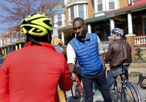 In this March 26, 2016 photo, Baltimore mayoral candidate DeRay Mckesson, right, chats with bicyclists as he canvasses in the Charles Village neighborhood of Baltimore. Mckesson is known on the national stage for his role in Black Lives Matter, but he's struggling as he campaigns for mayor in his hometown.