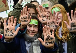"""Protesters in Berlin raise their hands to reveal the words: """"Our future in your hands"""""""