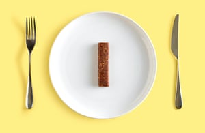 Cereal bar on white plate on yellow background, with knife and fork beside it