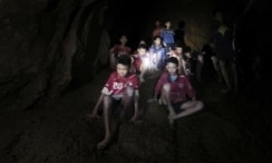 The 12 boys and their football coach pictured moments after they were found alive inside the cave complex.
