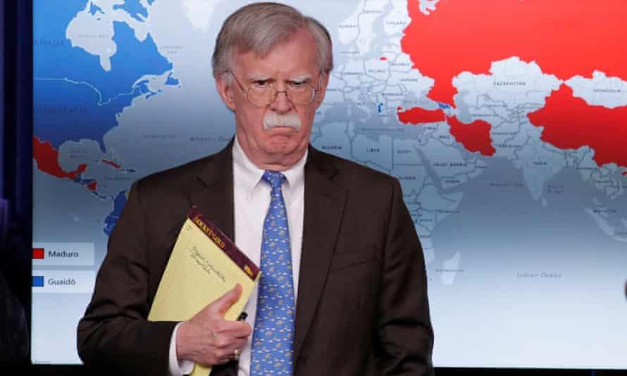 The US national security adviser, John Bolton, bearing notepad.