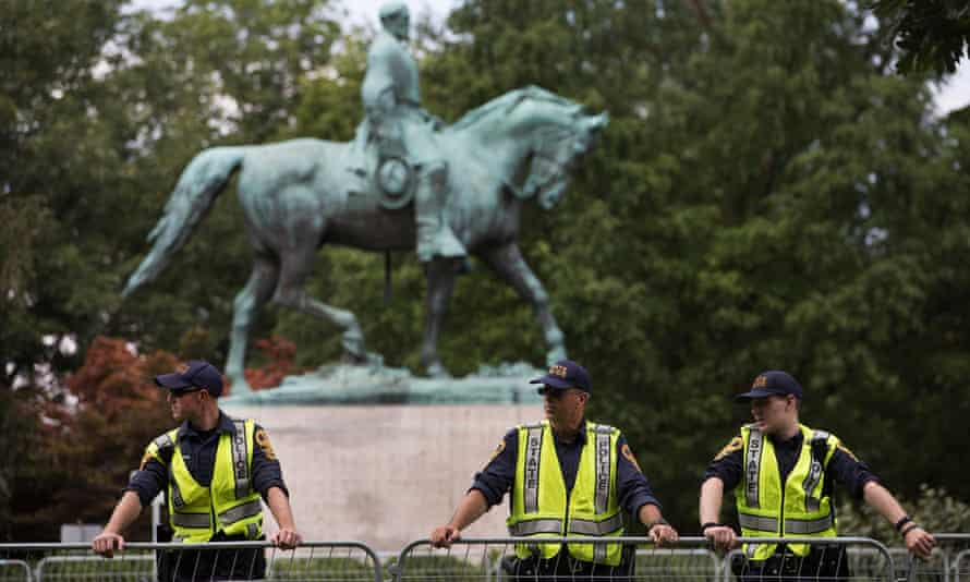 A heavy police presence in front of the statue of civil war Confederate General Robert E Lee.