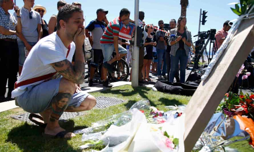 A man reads the dedications on bouquets of flowers near the scene of the attack in Nice