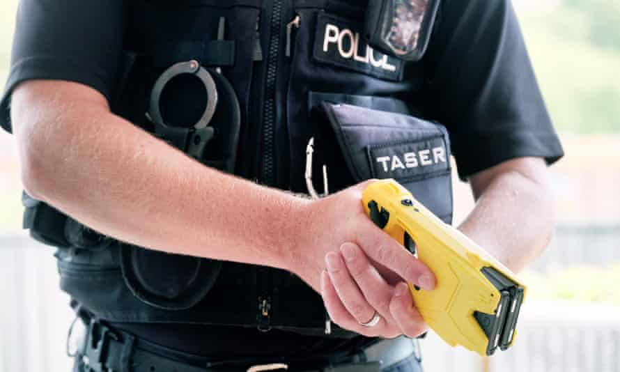 A British police officer holding a taser.