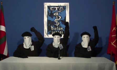 Masked members of the Basque separatist group Eta raise their fists in a familiar pose during a news conference in 2011