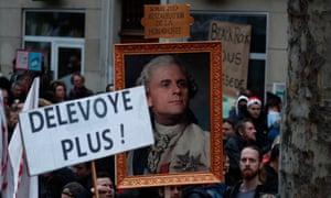 Protesters near Bastille Square in Paris hold a portrait of Emmanuel Macron