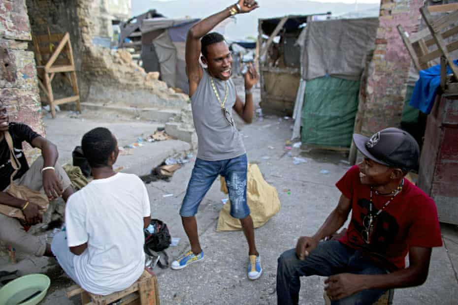 A man breaks into dance as he jokes around with friends, in the Grand Rue market area of Port-au-Prince, Haiti, Tuesday, June 16, 2015