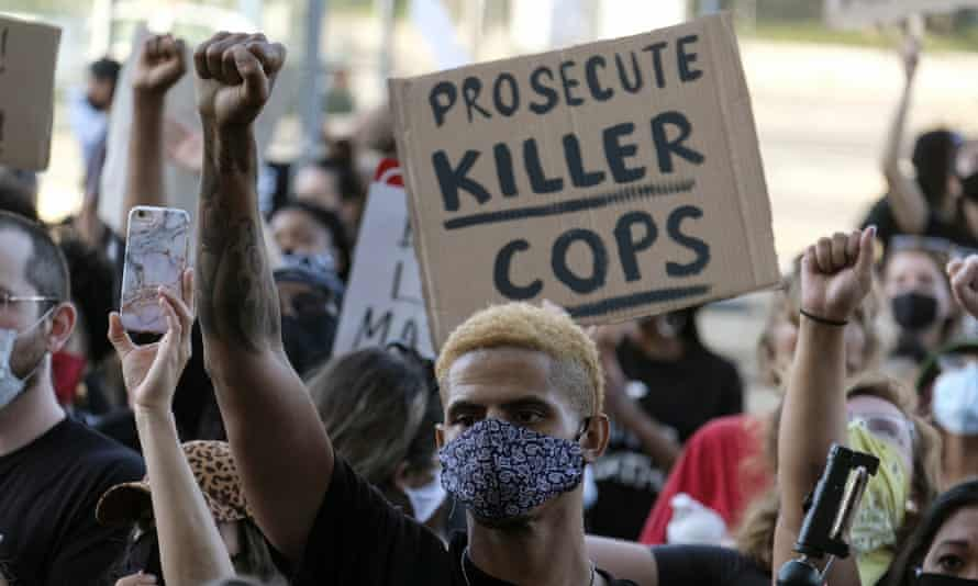 A demonstrator raises his fist during a protest of the death of George Floyd in downtown Los Angeles on 27 May.