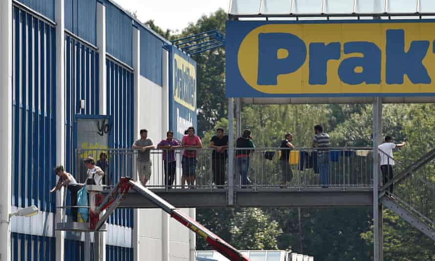 Asylum seekers stand on the steps of the new shelter in Heidenau, set up in a disused DIY store
