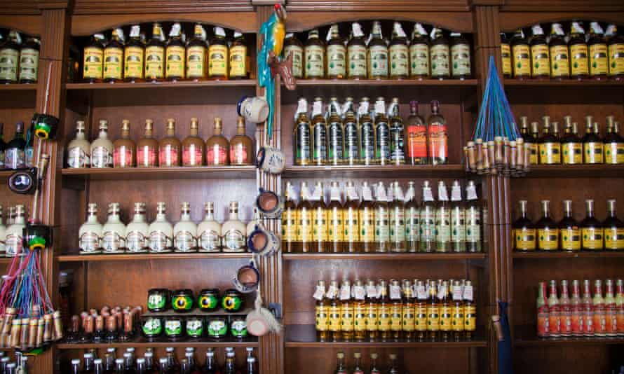 Bottles of mezcal and other spirits on sale in a shop.