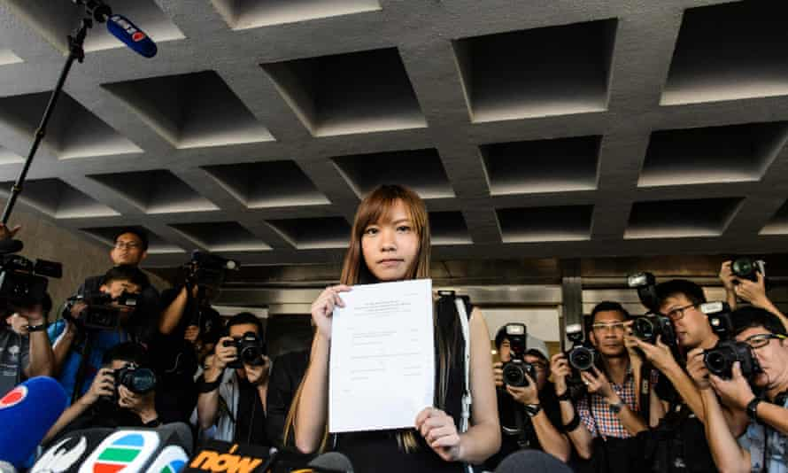 Yau Wai-ching holds the ruling banning her from taking her seat in the legislative council outside the high court in Hong Kong on Tuesday.