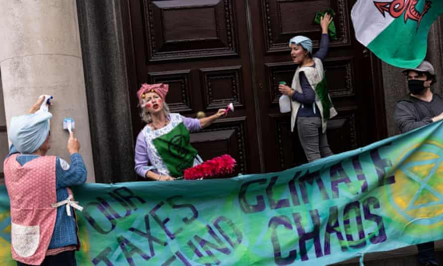 Extinction Rebellion activists scrubbing the doors of HMRC.