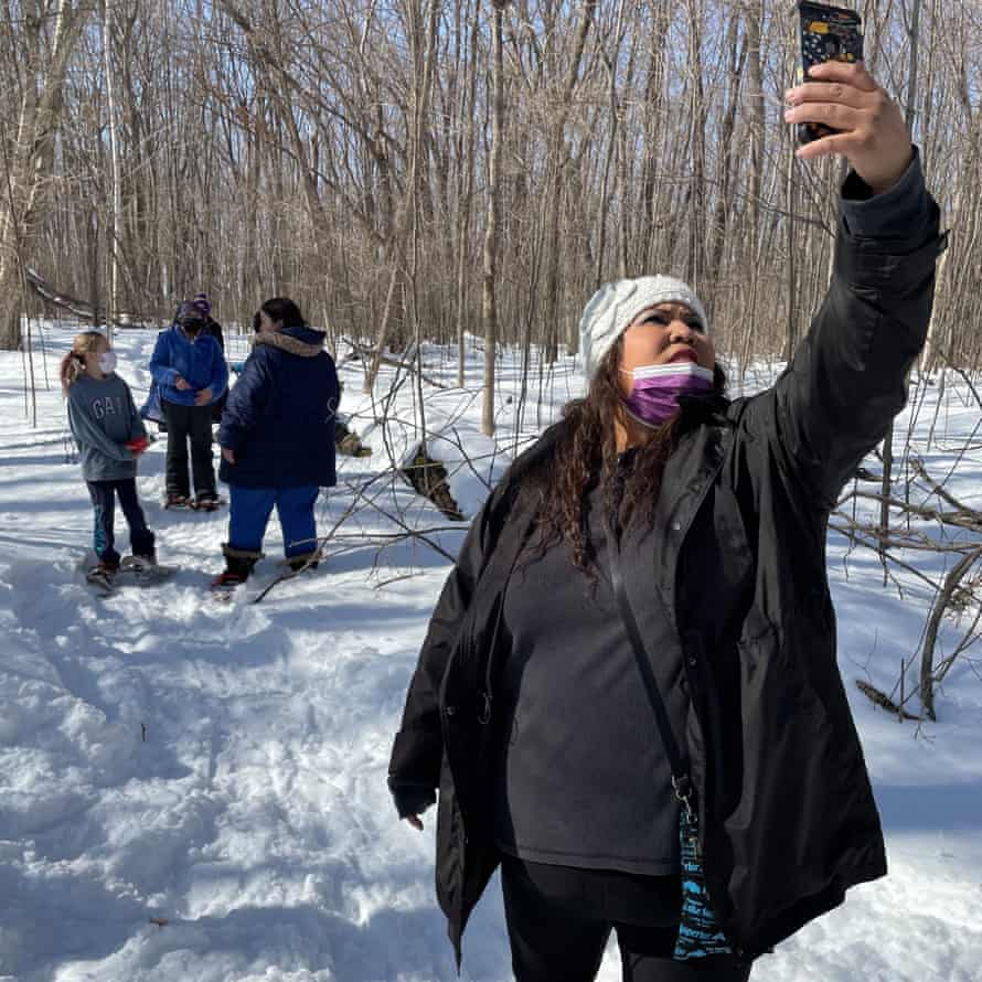 Bezhig Hunter, a fifth-grade teacher at Waadookodaading, holds her phone high so students who could not make the trip can participate virtually.
