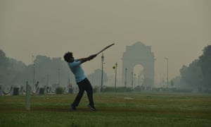 A boy playing cricket on a smoggy morning in New Delhi, India