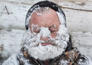 A hunter washes his face with snow