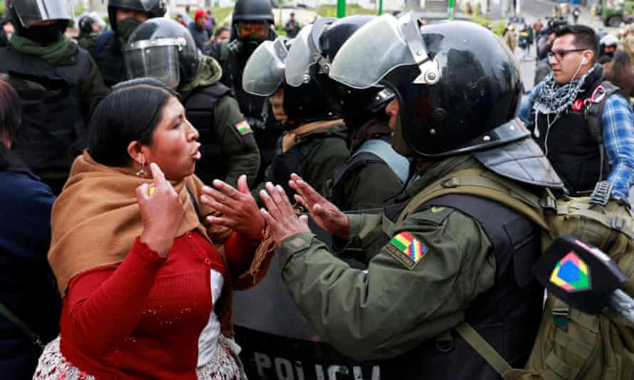 People react amid tear gas during clashes between members of the security forces and supporters of former Bolivian President Evo Morales in La Paz<br>A woman argues with a member of the security forces during clashes between members of the security forces and supporters of former Bolivian President Evo Morales in La Paz, Bolivia November 13, 2019. REUTERS/Henry Romero