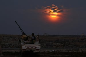 A Free Syrian army fighter sits on a pickup truck