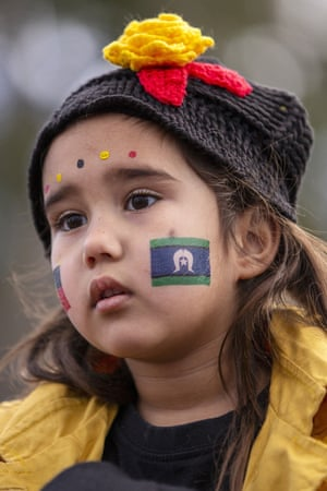A young girl with Aboriginal and Torres Strait Islander flags painted on her cheeks