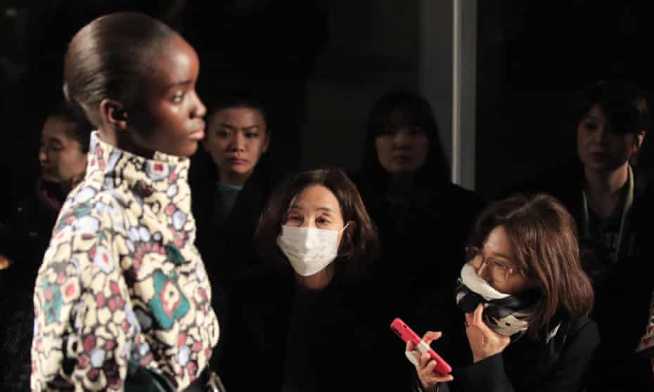 Women in protective masks watch a model at the Isabel Marant show at Paris fashion week.