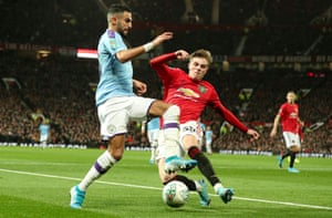 Brandon Williams of Manchester United dives in to a challenge on City's Riyad Mahrez.
