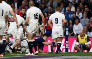 Scotland's Huw Jones stretches out an arm to score a try.