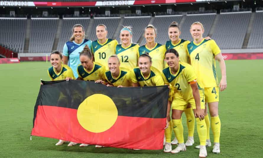 Australian players pose with an Aboriginal flag