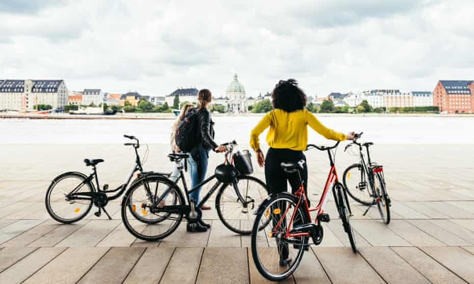 Guide and guest with bicycles in Copenhagen on Foods of Copenhagen tour.