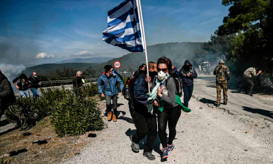 A demonstrator holding a Greek flag runs from riot police