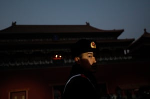 A Chinese police officer is partly illuminated before the the Forbidden City or Palace Museum lights up
