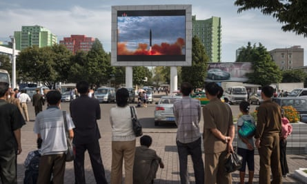 People watch as a screen shows footage of the launch of a Hwasong-12 rocket in Pyongyang on Saturday.