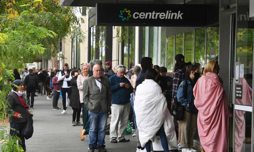 People queue outside an Australian government welfare centre, Centrelink, in Melbourne on 23 March 2020