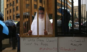 An Abaad activist dressed as a bride and wearing bandages stands in a golden cage in a protest in downtown Beirut.