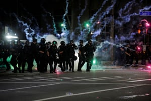 Flares go off in front of police officers during a protest over the death of Daniel Prude on Friday night.