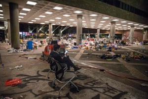 A man looks at his phone in front of debris at the Hong Kong Polytechnic University