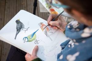 A still from RSPB Big Garden Birdwatch TV advertisement showing artist Angela Hennessey painting birds while taking part in the national birdwatch in Bristol