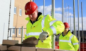 David Cameron in a hard hat and high vis jacket lays a brick on a building site