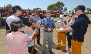 Michelle Henderson, third from right, on the job for AAP, one week before Black Saturday in 2009, when the Bunyip fires were burning in Gippsland. Speaking is the former Victorian premier John Brumby.