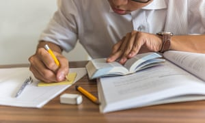 Young student writing into a sticky note