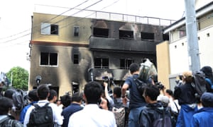 People gather around a Kyoto Animation studio building after an arson attack.