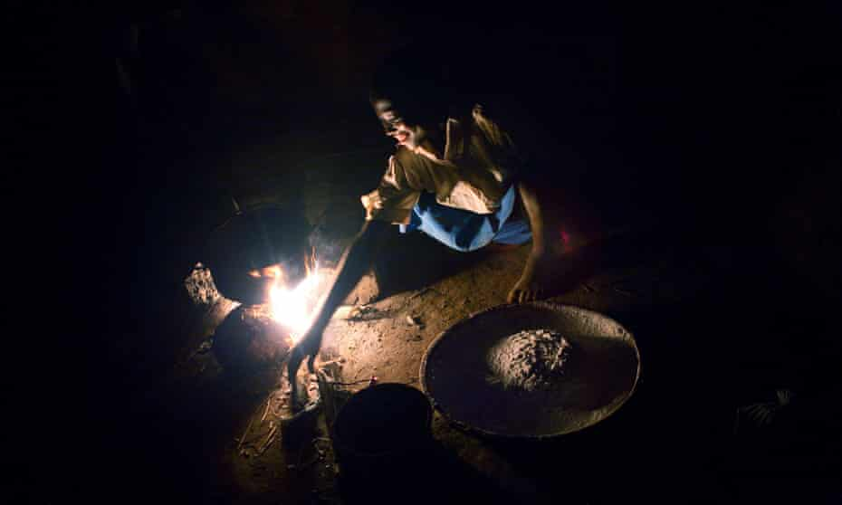 Mwaiwawo Mphandula, 13, cooks maize porridge in the kitchen of the family house as the sun goes down, in a village 30 miles from Lilongwe