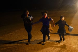 Three children hold hands as they run in the rain at an intake area in Roma, Texas, after turning themselves in upon crossing the border into the US from Mexico