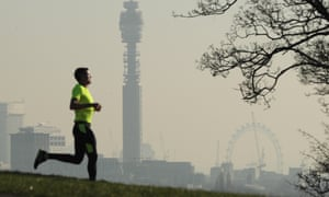 A view of smoggy London skyline from Primrose Hill and man running.