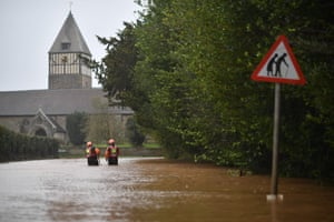 Fire and rescue personnel check the depth of flood water as they walk along a flooded road in the village of Hampton Bishop in Herefordshire.