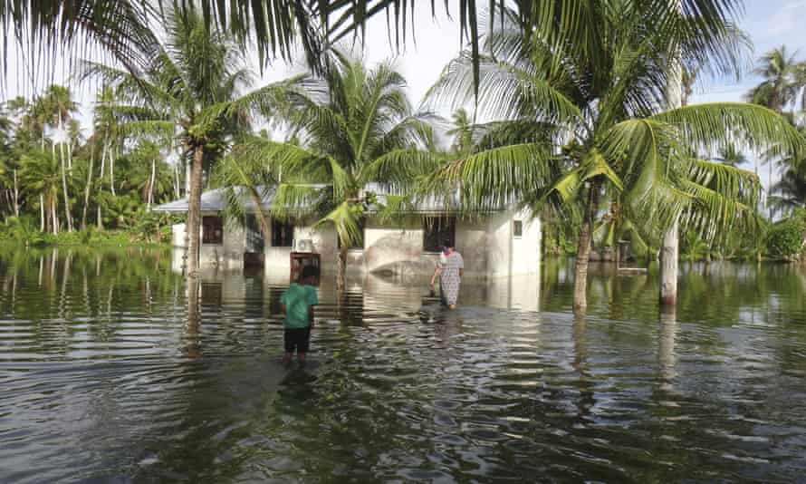 A woman and a child walk through knee deep water to reach their home during a king tide event on Kili in the Marshall Islands. Climate change poses an existential threat to places like the Marshall Islands, which protrude only two metres above sea level in most places.