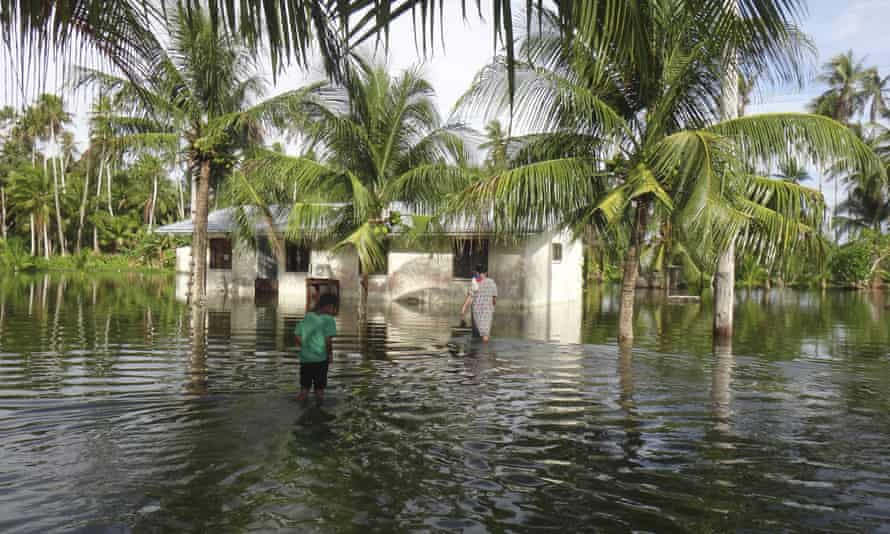 A woman and a child walk through water to reach their home during a king tide event on Kili in the Marshall Islands
