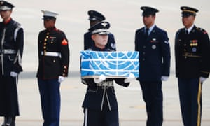 A soldier carries a casket containing the remains of a US soldier killed during the Korean war, after arriving from North Korea at Osan Air Base in Pyeongtaek, South Korea on 27 July.