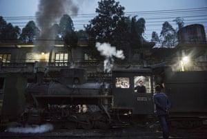 A railway engineer preps a coal powered steam train before departing Shixi