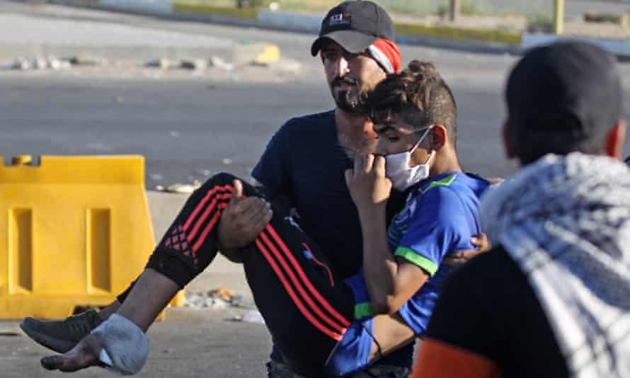 Protester carries a wounded man