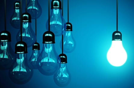 Lightbulbs against blue background, one (set apart on right) switched on
