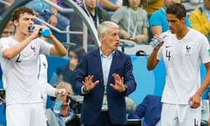 France's Benjamin Pavard (left) and Raphael Varane listen to instructions from their manager, Didier Deschamps, mid-match.